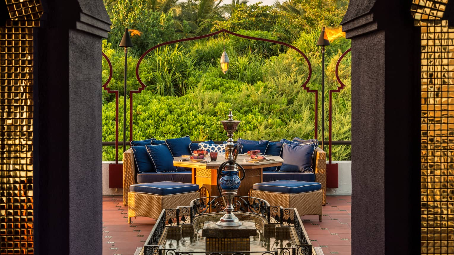 Shisha pipe on platform in front of plush blue patio sofa, dining table, tropical gardens