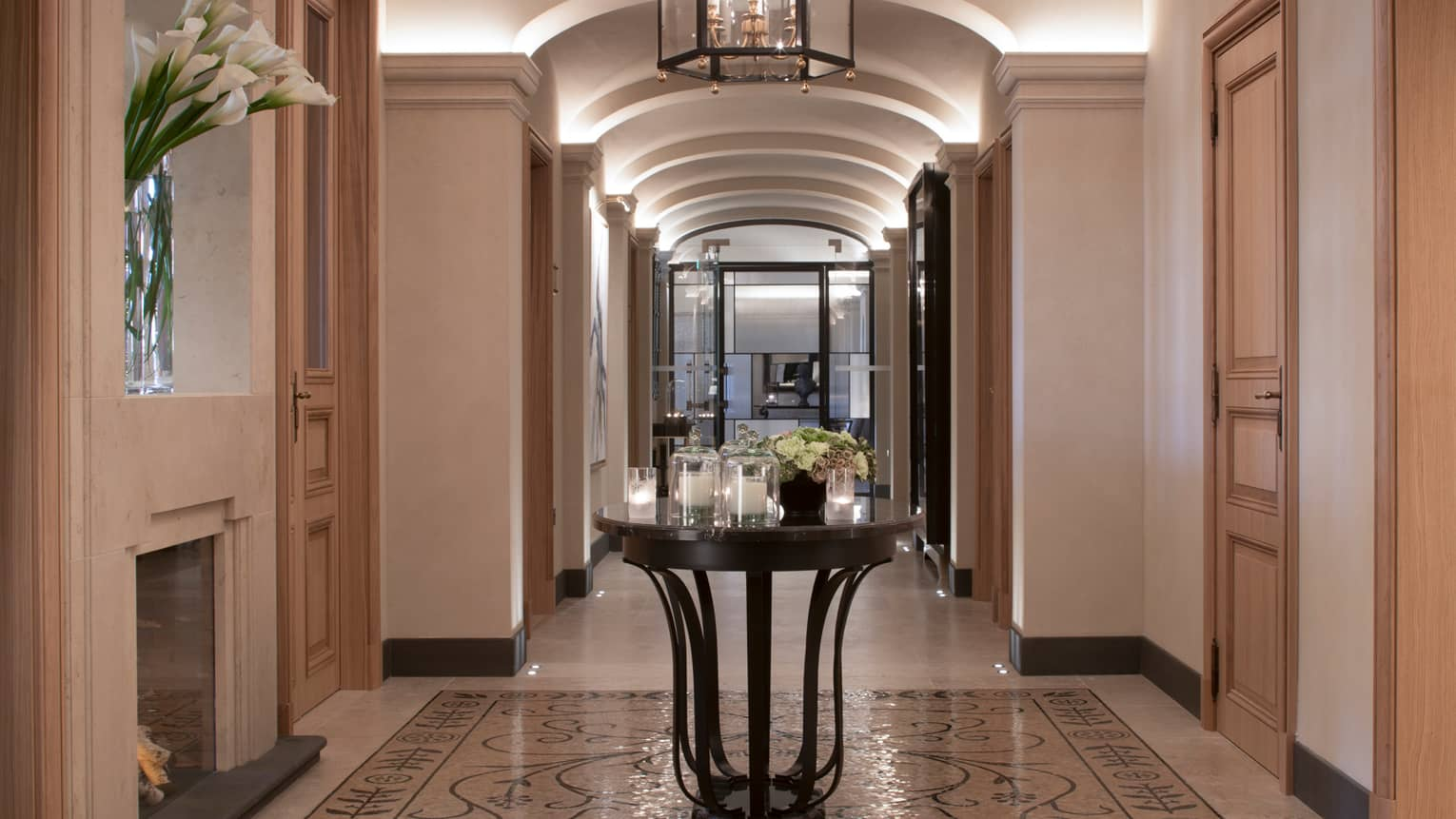 Hotel hallway with marble floors, round table with multiple white candles in glass votives, fresh flowers