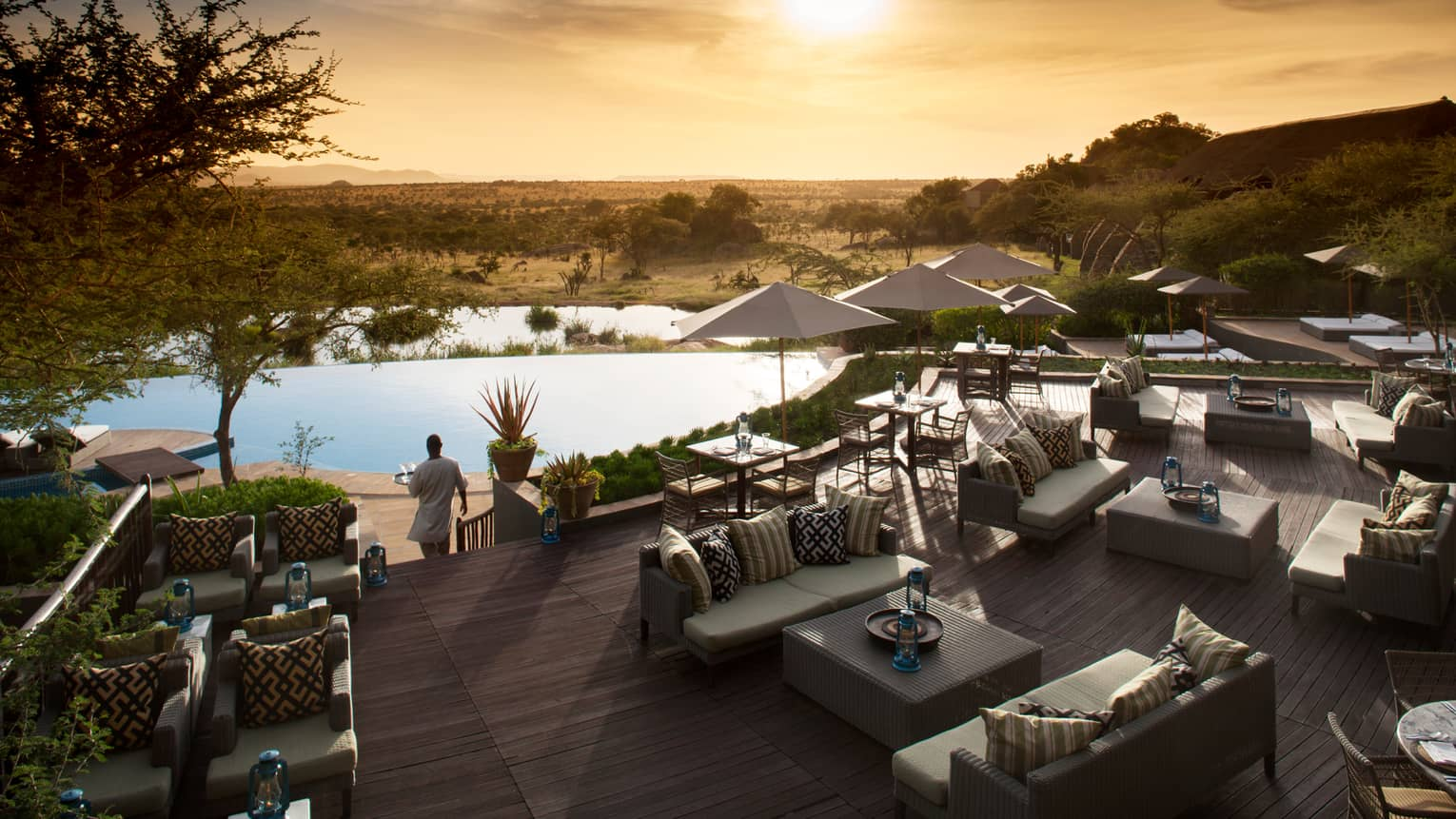 Server carries tray through Terrace Bar outdoor patio by lounge chairs, swimming pool at sunset