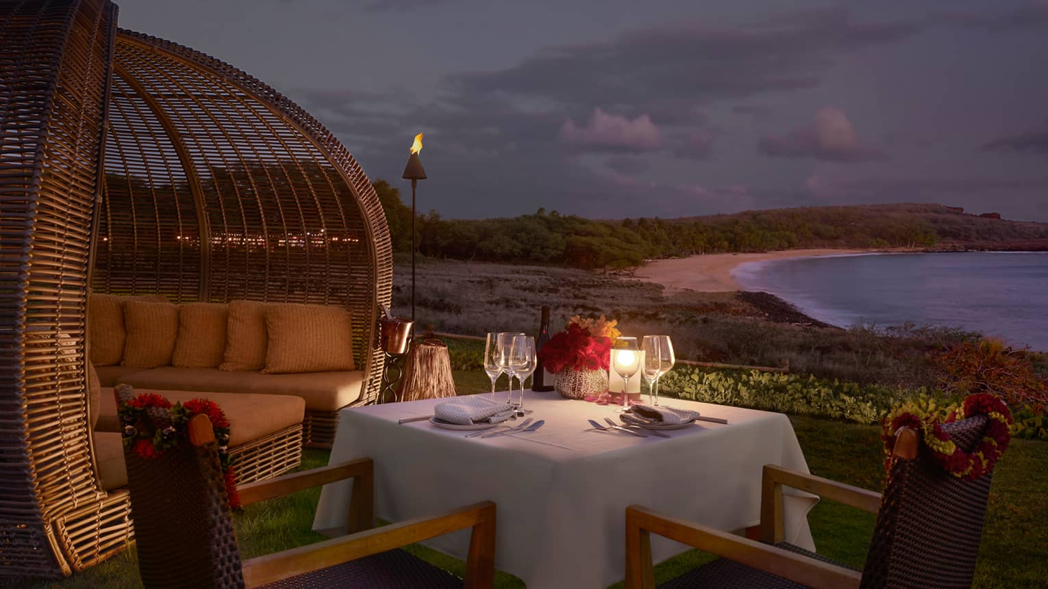 Candle-lit, private dining table with white cloth on patio by cabana, beach, ocean at night