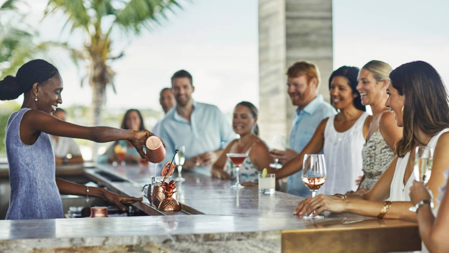 Smiling mixologist pours cocktail as guests sit around sunny bar