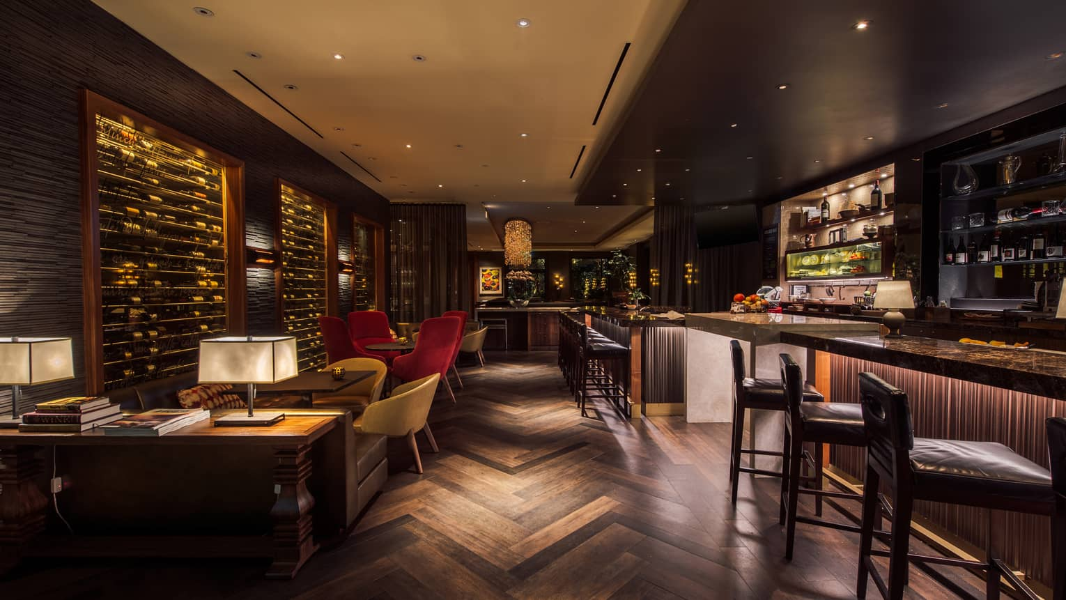 Dimly lit, indoor wine bar with geometric wooden floor, bar, wall of wine bottles