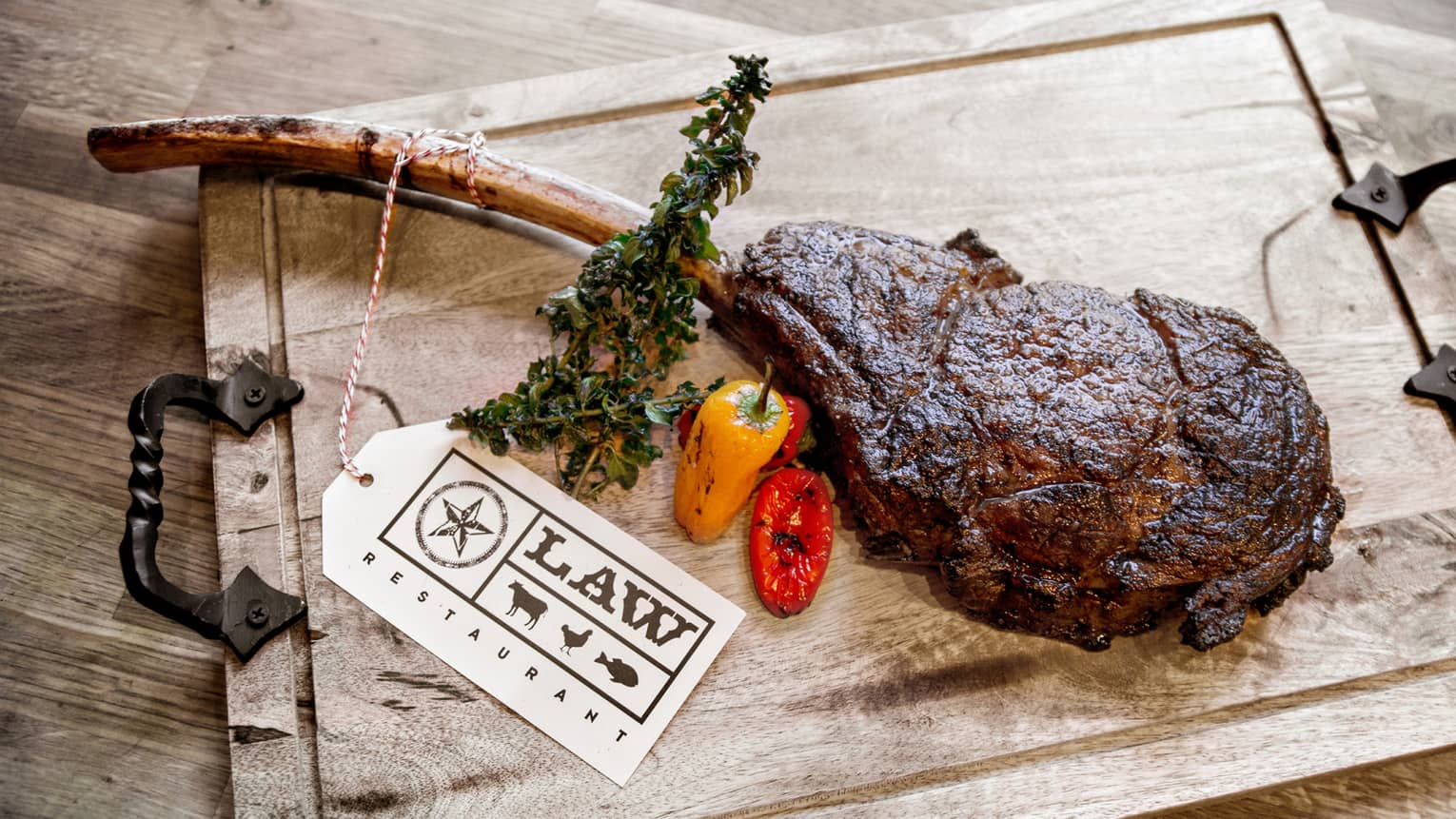 Forty-eight ounce, Long-Bone Tomahawk steak chop on wood platter with roasted peppers, sign
