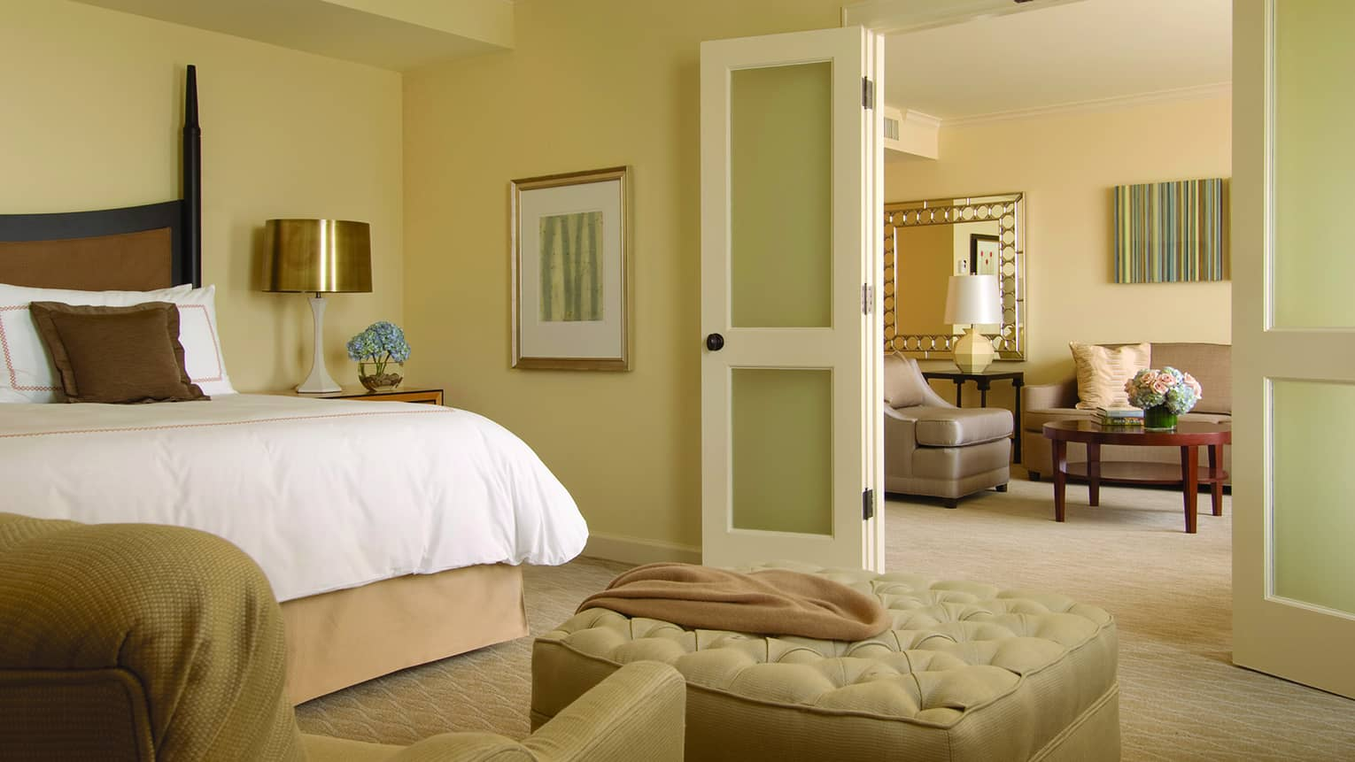 Executive suite bedroom with bed, large beige ottoman, French doors opening to living area