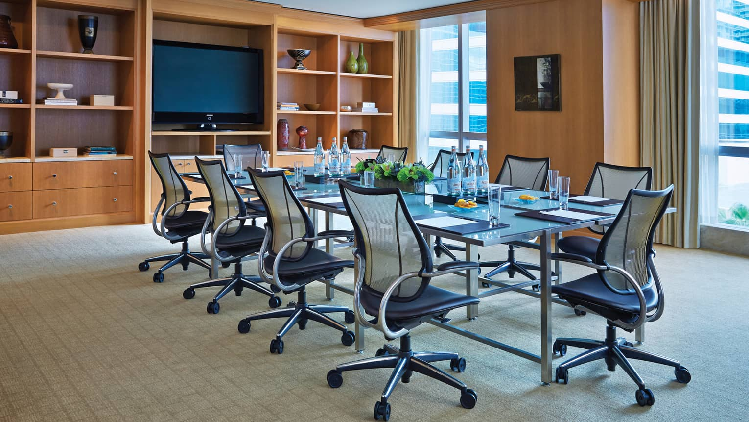 Swivel chairs line boardroom table in bright meeting room with shelves