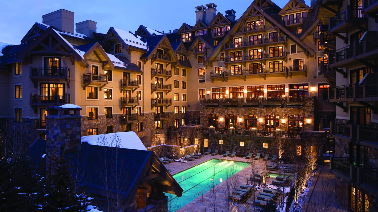 Four Seasons Vail hotel exterior at night with lit windows and balconies, glowing blue outdoor swimming pool