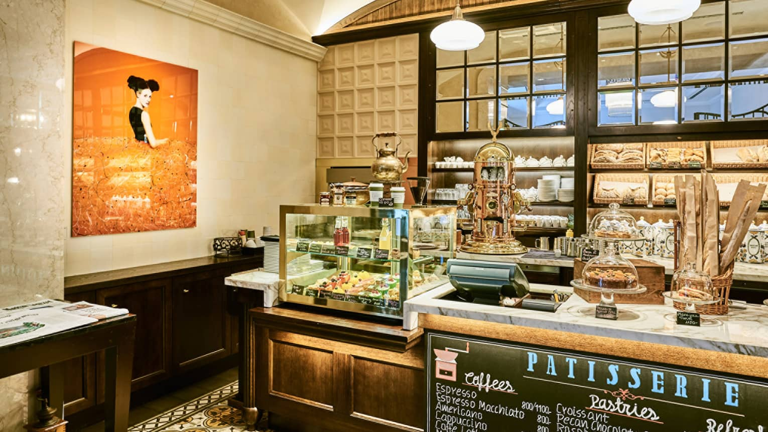 KOLLÁZS Brasserie & Bar Patisserie counter with pastries, bread in display case, large orange painting