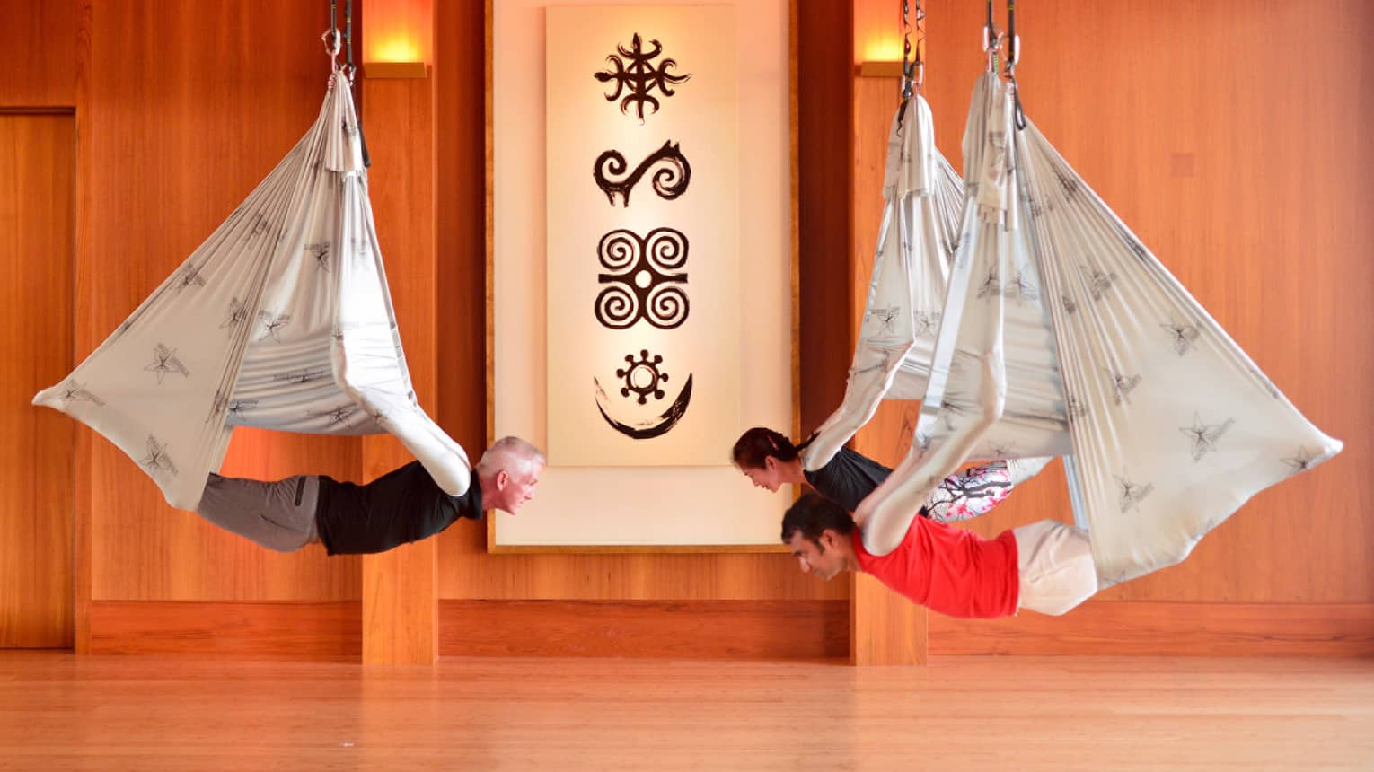 Men, woman hang from silk hammocks during anti-gravity yoga session