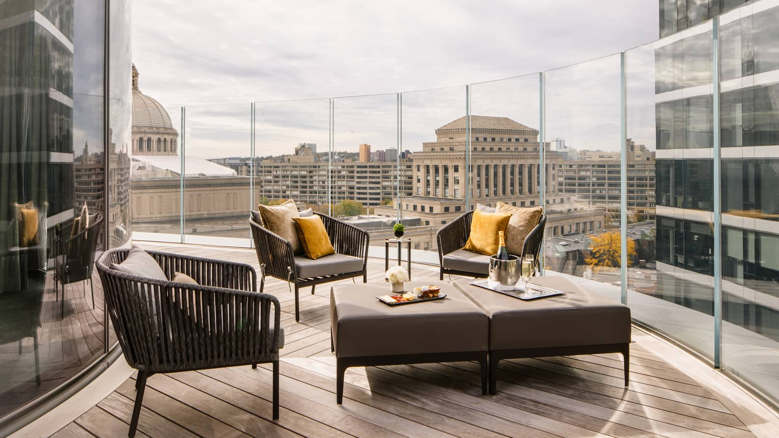 Wrap-around balcony with grey lounge chairs and table, view of Boston skyline