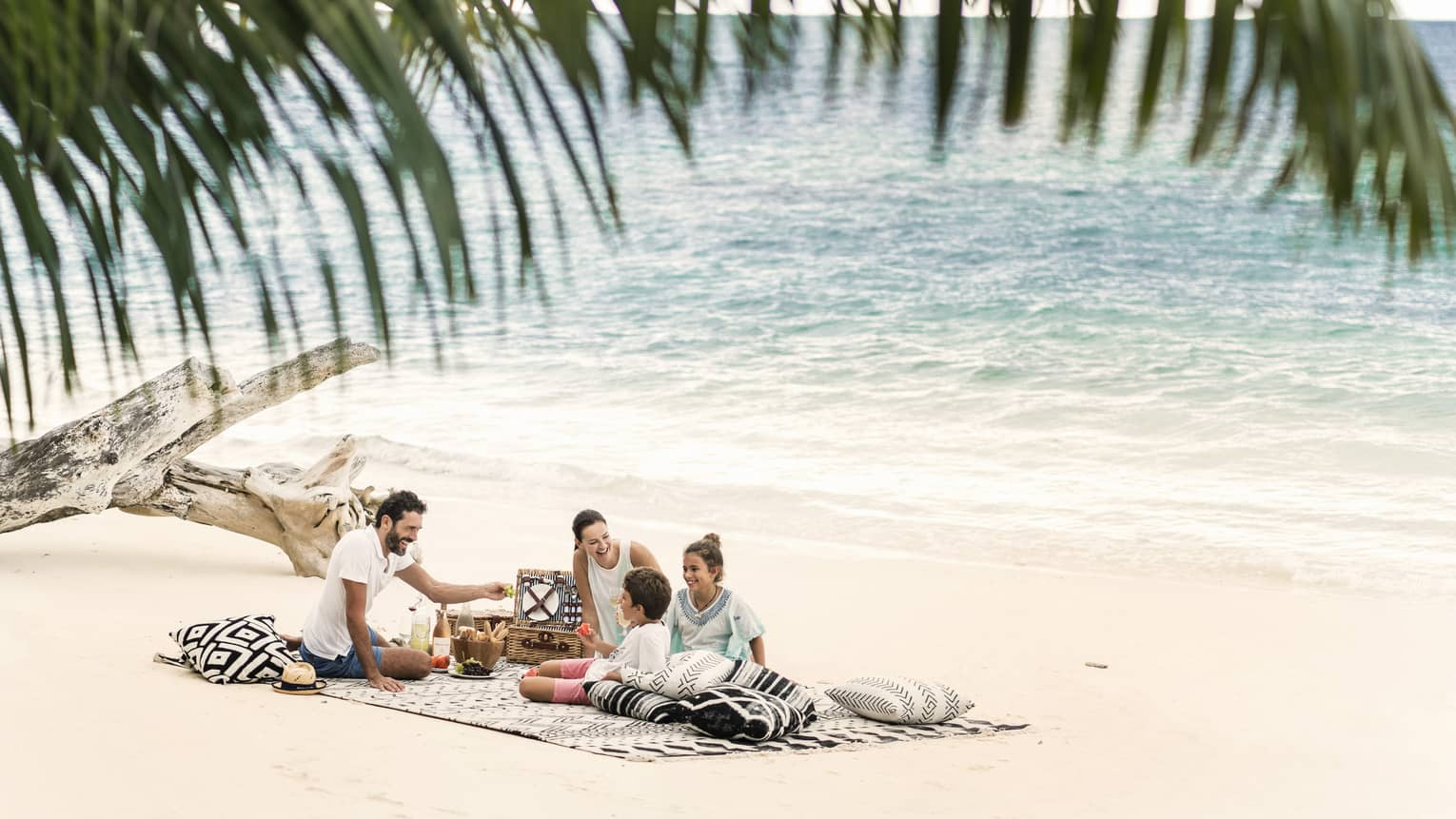 A man, woman and two children picnic on the beach just a couple feet away from the ocean.