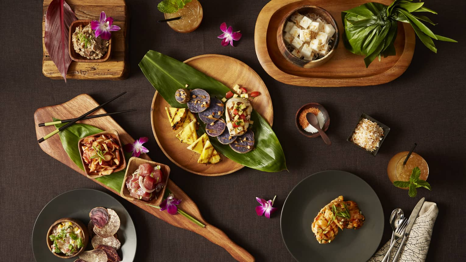 Aerial view of wooden bowls with contemporary food, garnished with large leaves, orchids and chopsticks