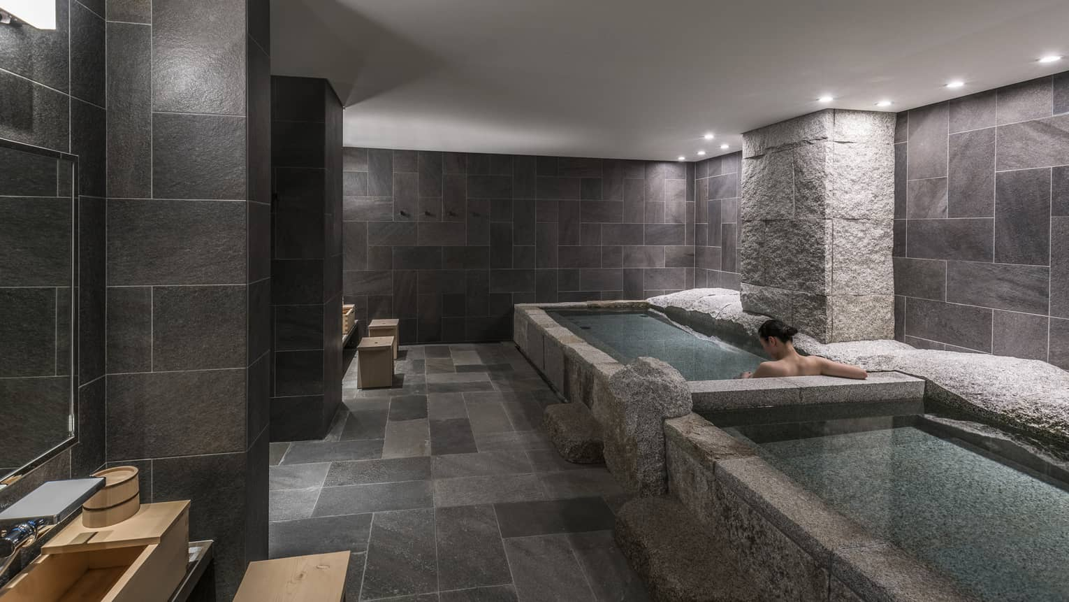 Back of woman's bare shoulders and she soaks in spa tub in tile, granite room