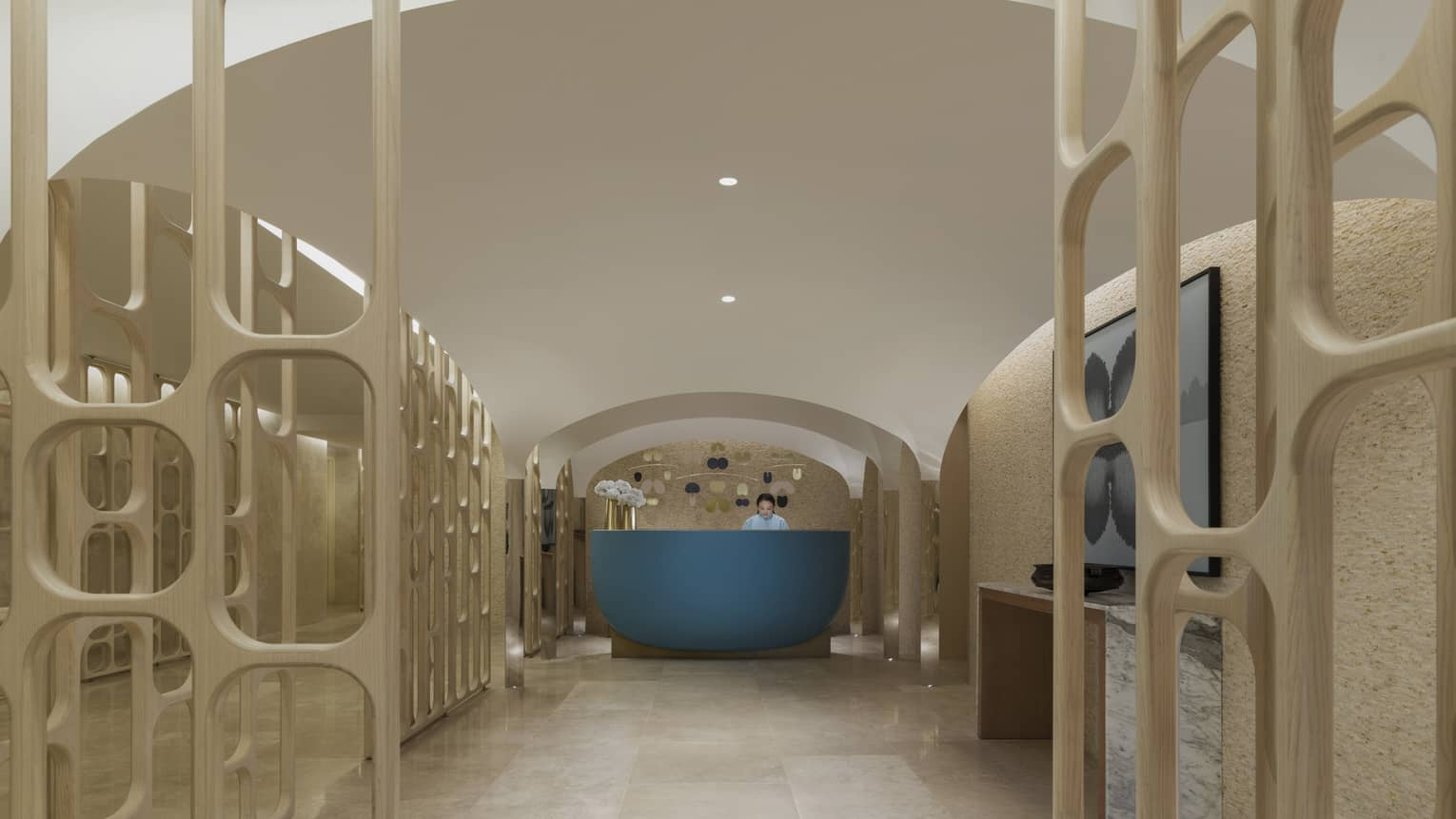 The spa entrance is marked by a blue desk sits on a marble floor