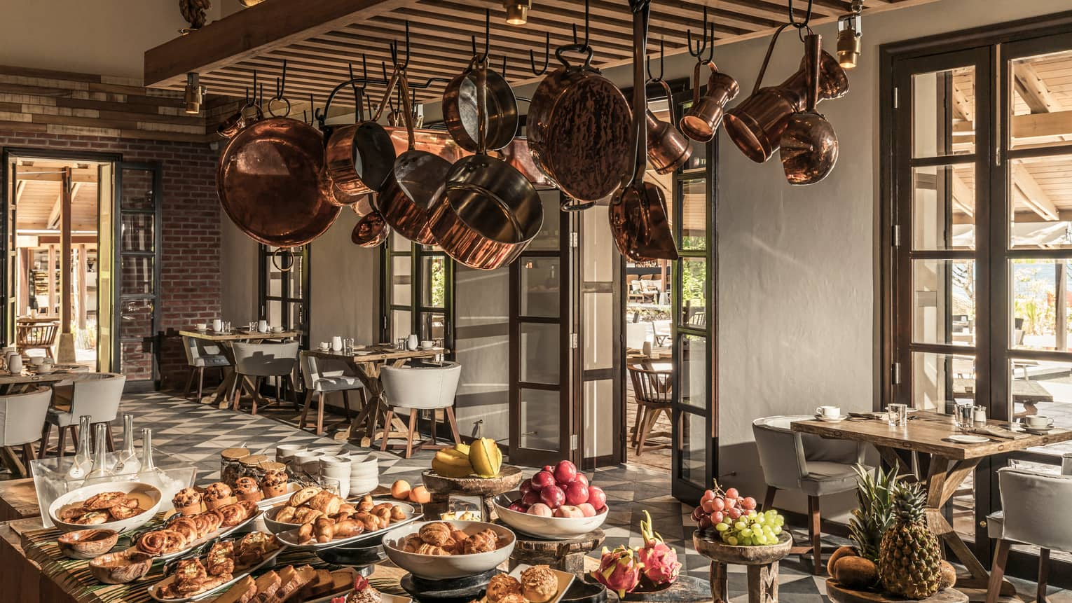 Claudine restaurant interior with hanging copper pots over buffet