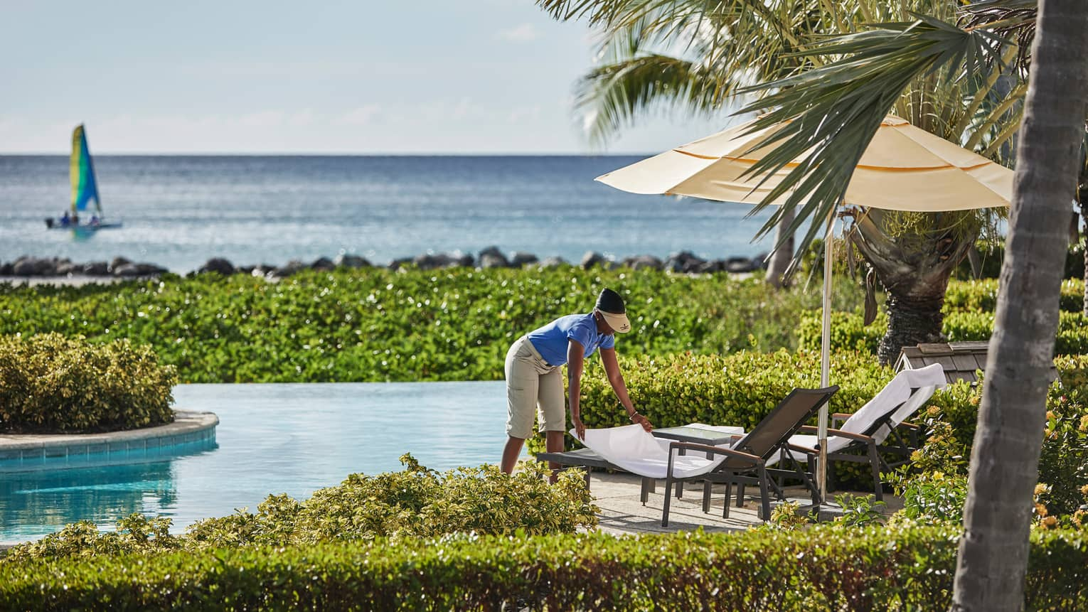 Hotel staff sets patio chair on Ocean Pool deck, boat sailing on Caribbean Sea