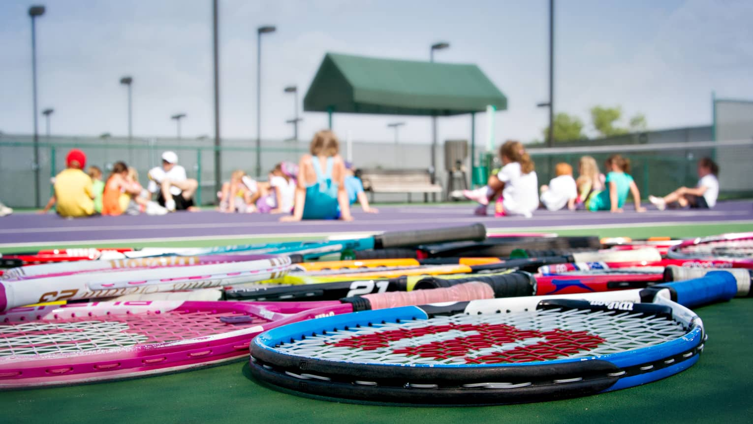 Colourful tennis rackets lying on ground, children sit cross-legged on court