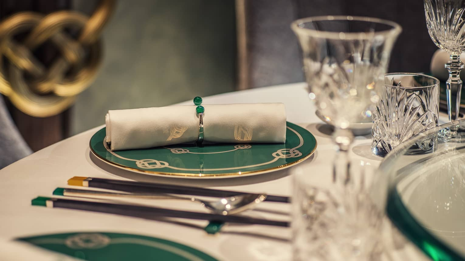 Yu Yuan close-up of rolled white napkin on green-and-gold plate, crystal glasses