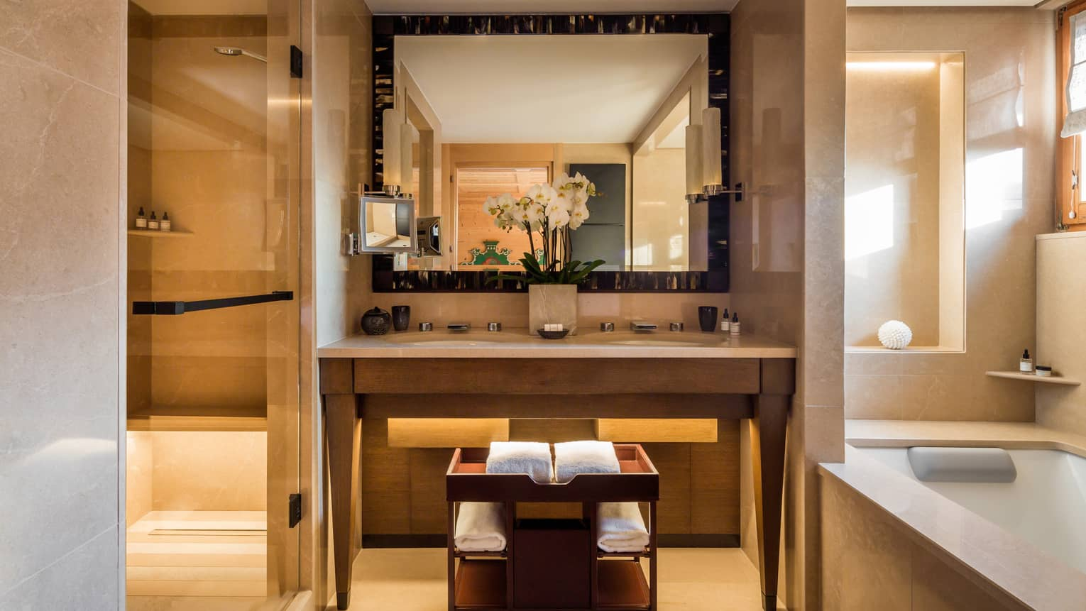Modern with bathroom double sink vanity and mirror, orchids beside tile bath tub