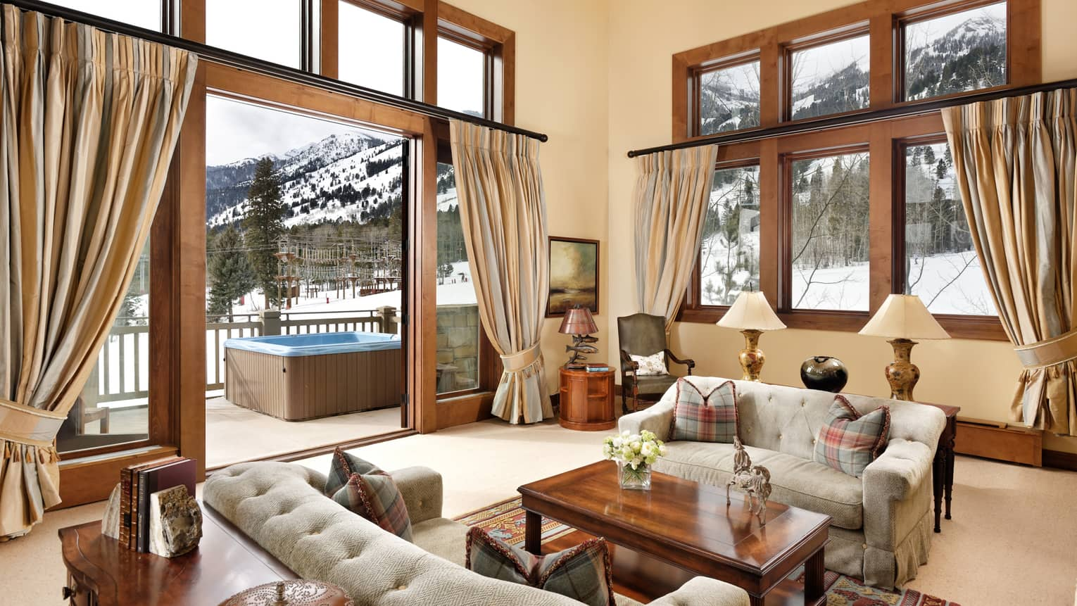 Large bright living room with open door to winter patio with whirlpool, snow covered mountain