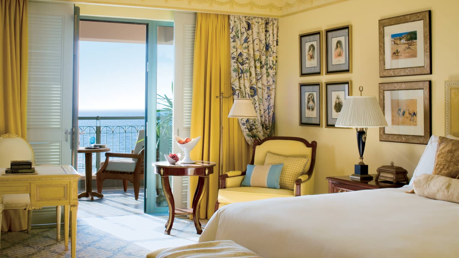 Sea-View Room with warm yellow walls, decor and floral accents, open patio door with Mediterranean Sea view