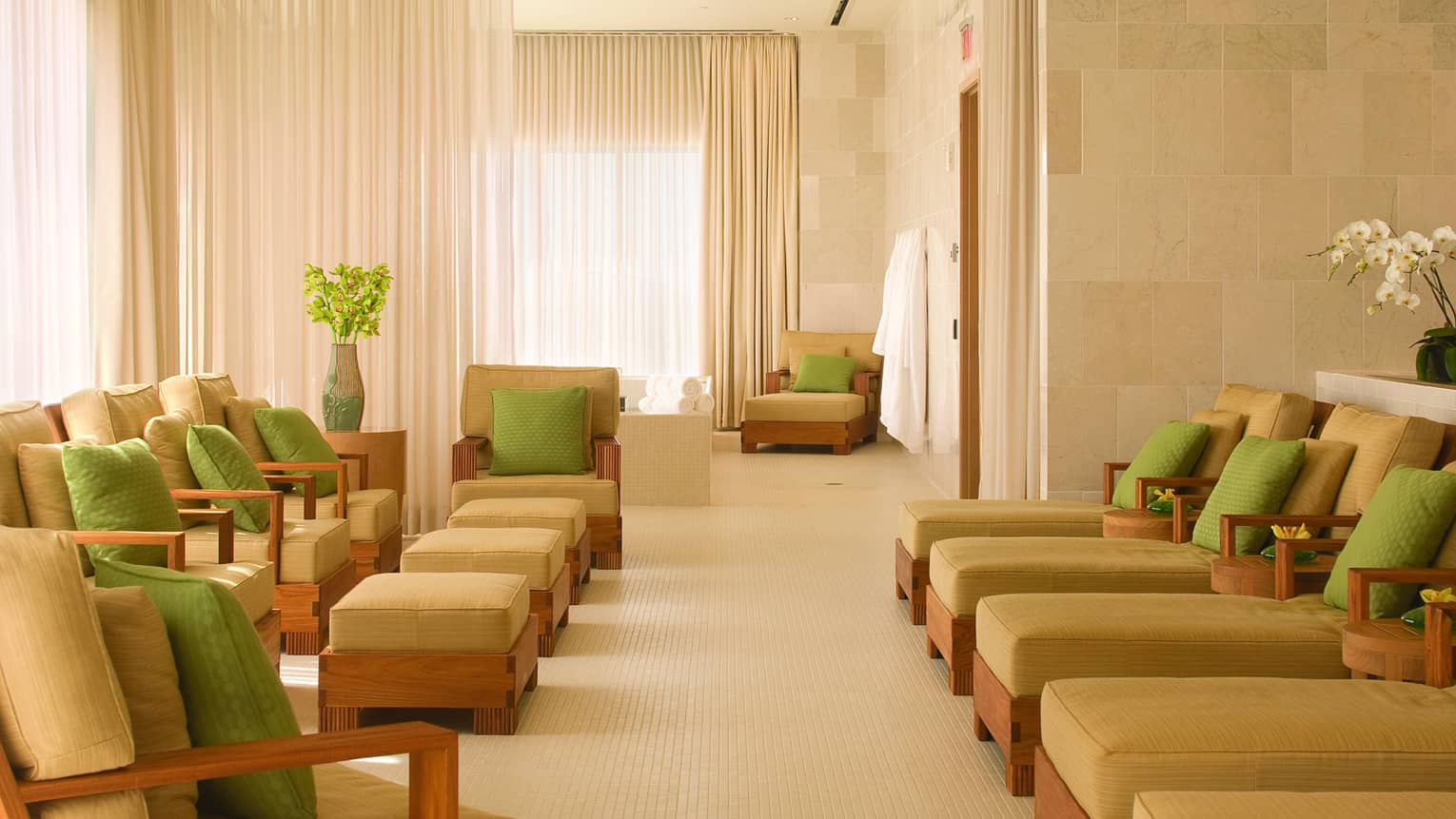 Spa lounge with rows of plush beige chairs and chaise lounges with lime green accent pillows