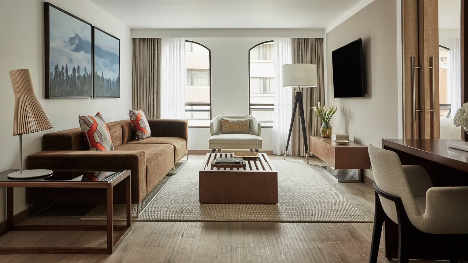 Four Seasons Executive Suite light-filled living room with brown sofa, white chairs, wood tables