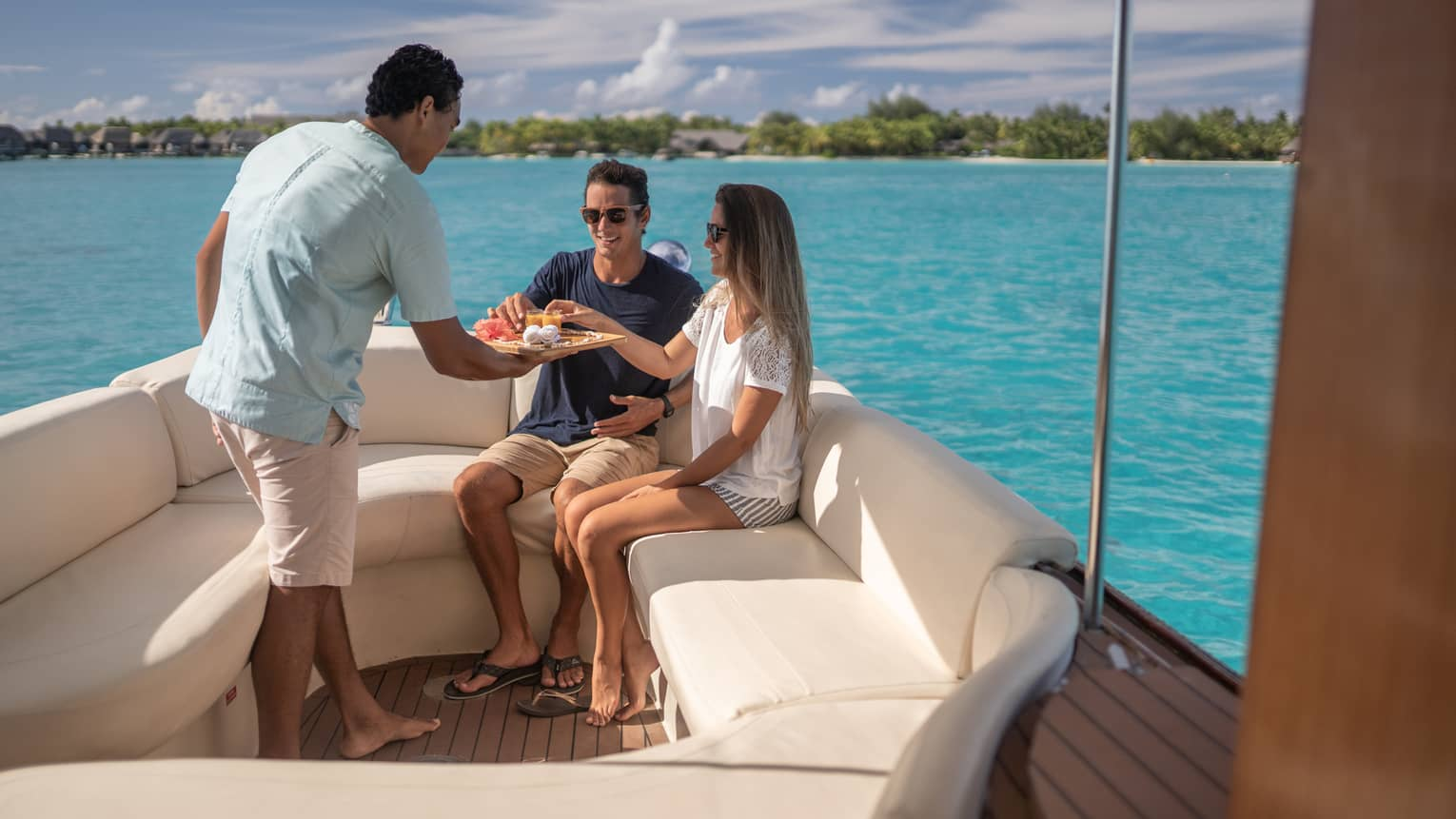 Staff serves juice to couple at edge of yacht on Bora Bora lagoon