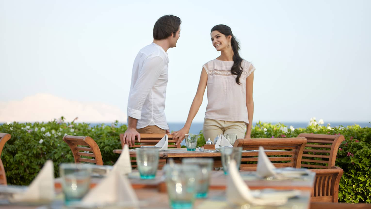 Smiling man and woman stand by wood patio chairs, dining table at Reef Grill