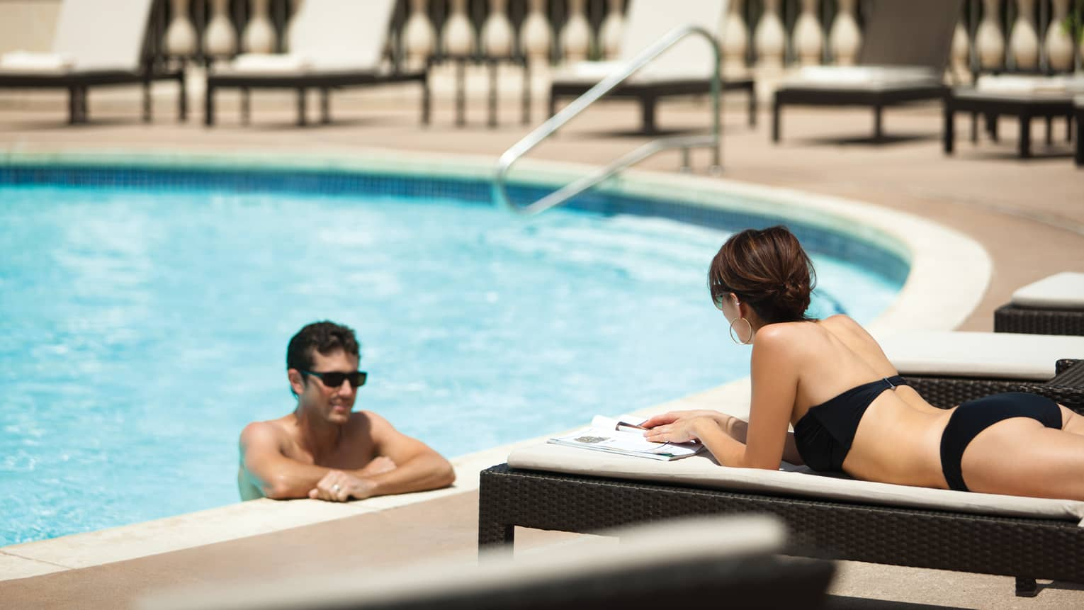 Man wades at edge of outdoor swimming pool, looks up at woman lying on deck chair