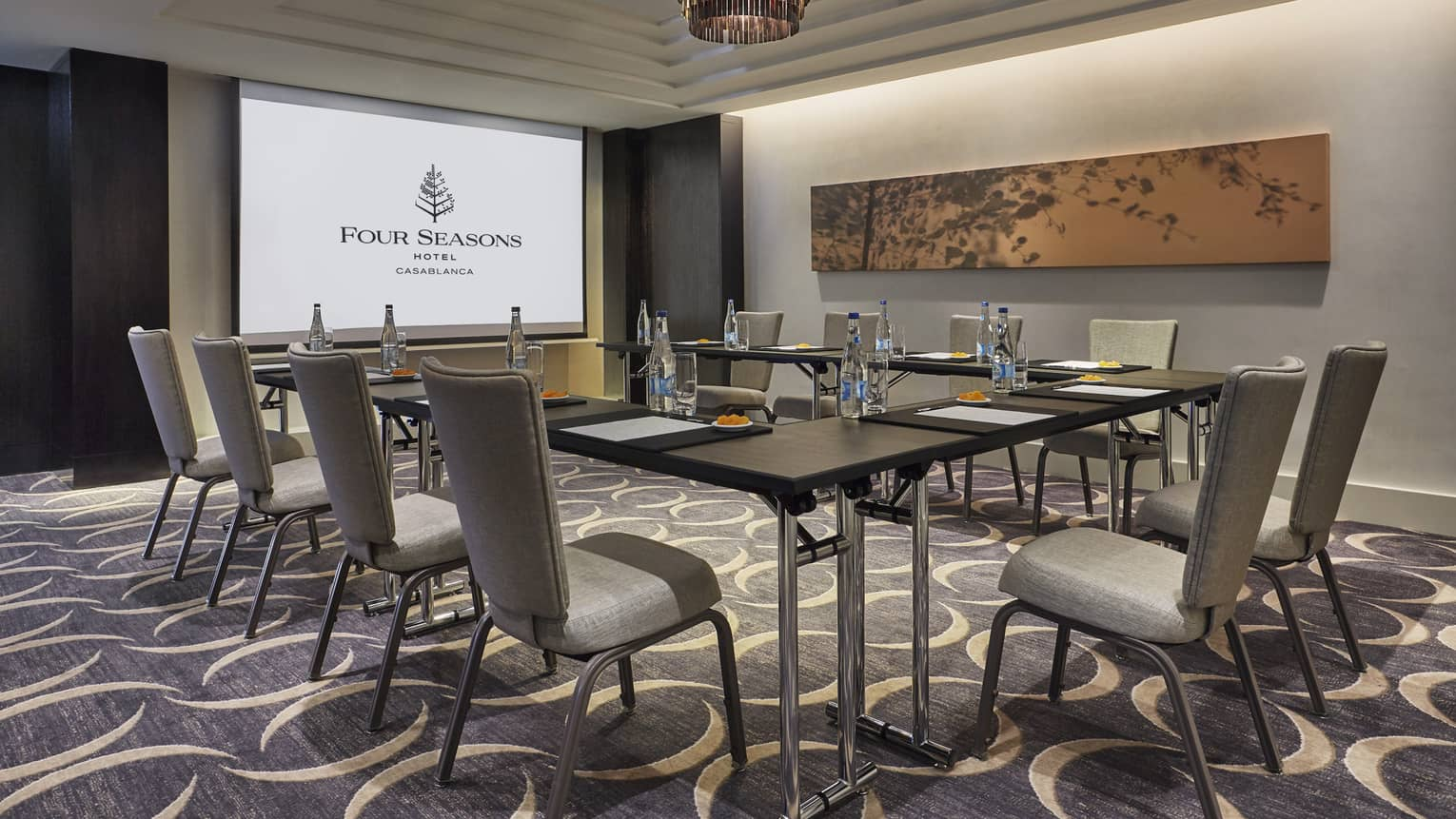 Business meeting room with large screen with Four Seasons logo, tables and chairs