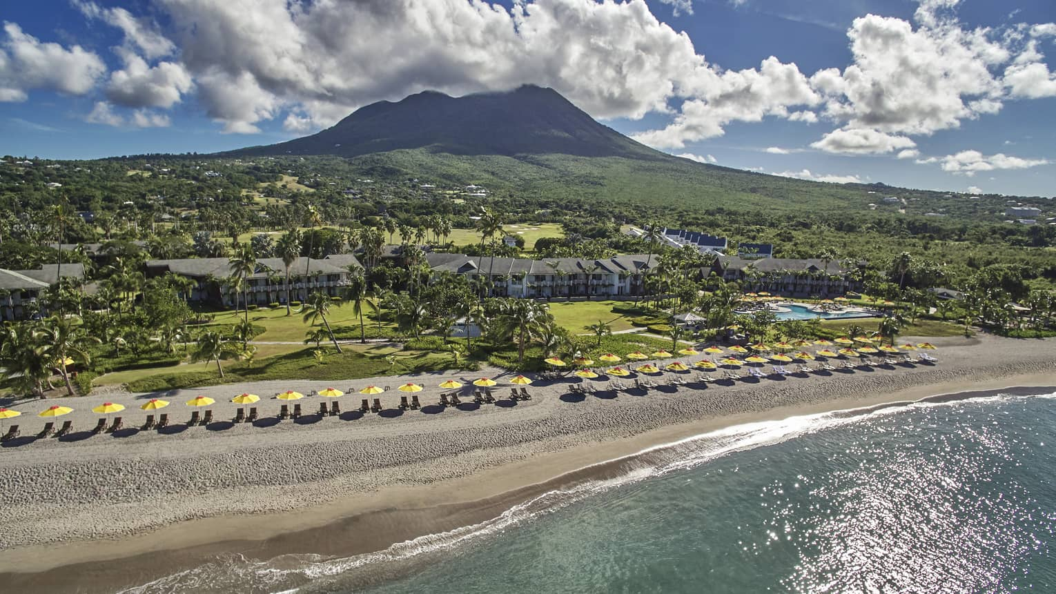 View over Four Seasons Resort Nevis, yellow umbrellas line beach, mountain, clouds