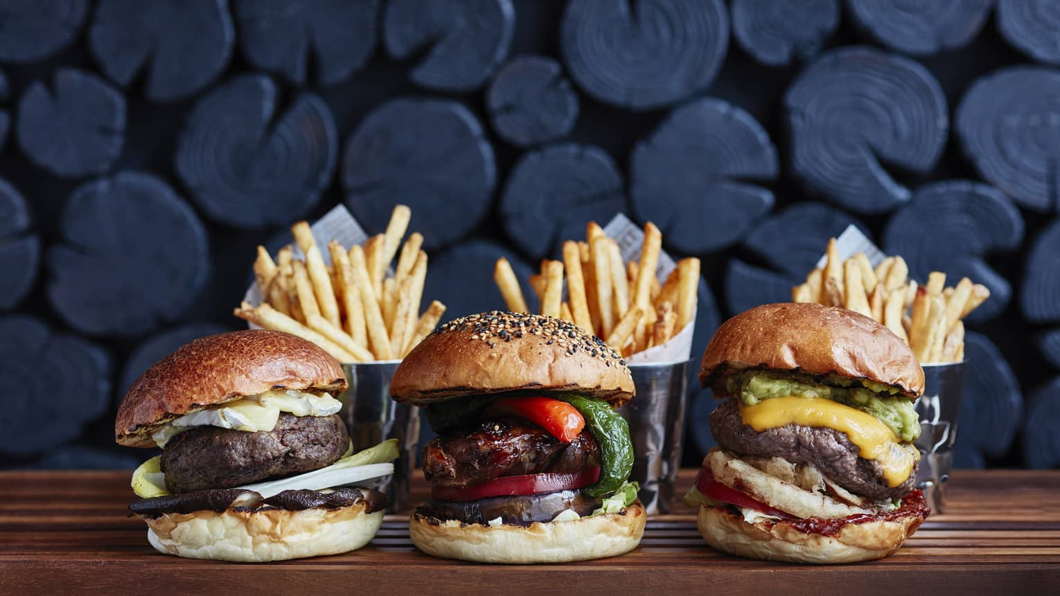 Three hamburgers with Brie, black truffles, duck confit and french fries on the side