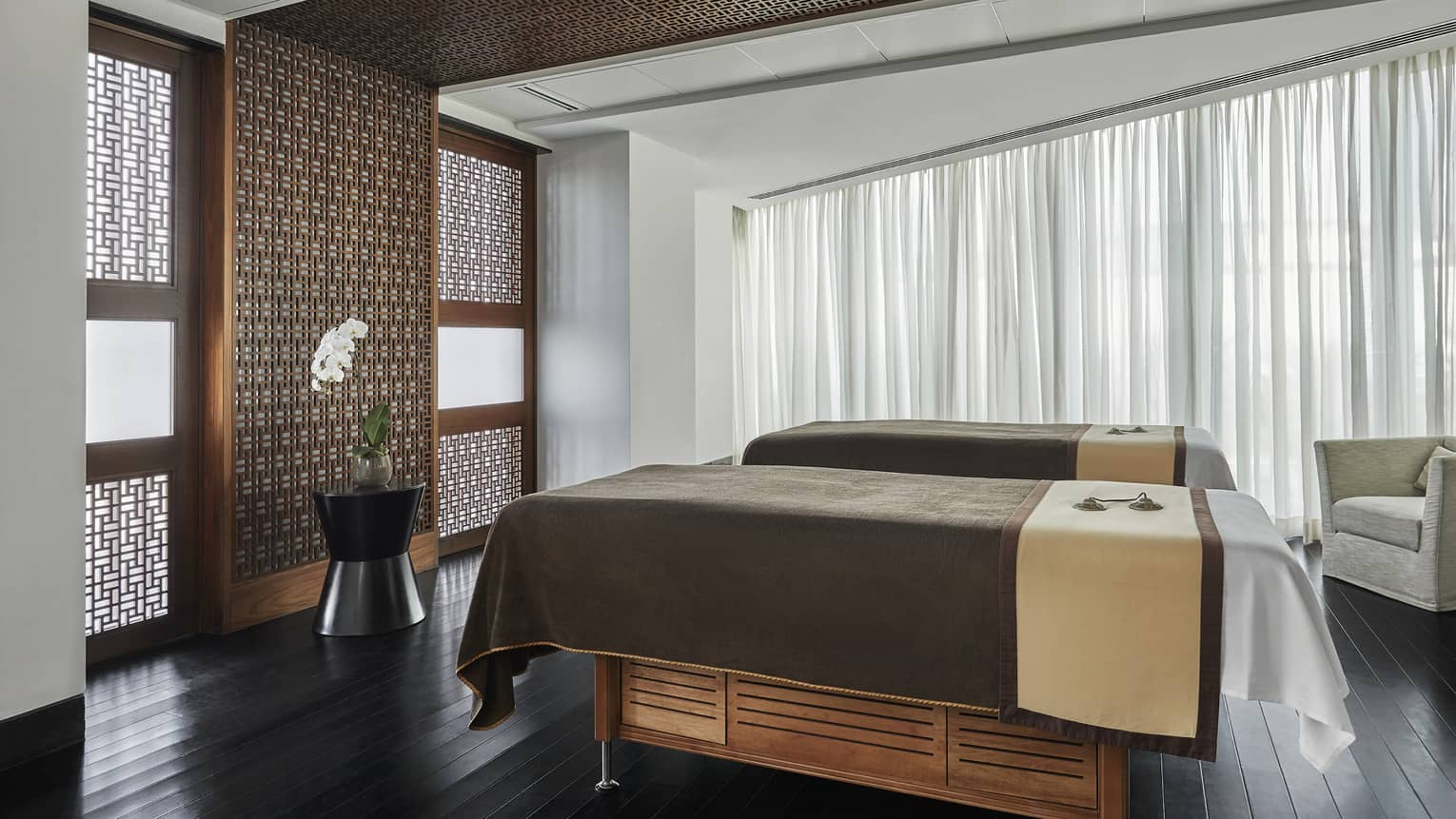 Pearl Spa side by side couples massage beds in treatment room with wood accent walls
