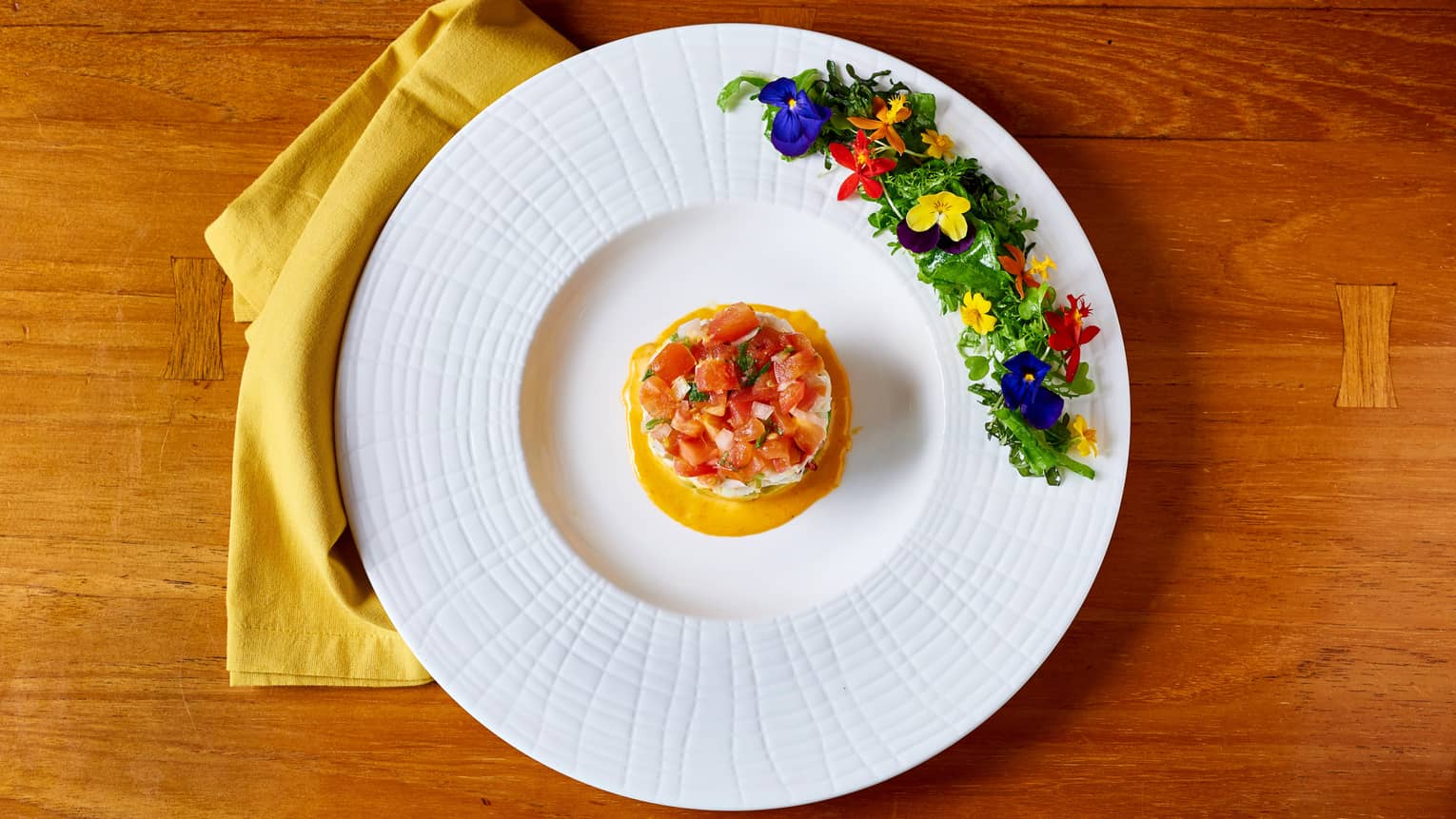 Aerial view of Lobster Tower cold seafood dish lined with edible flowers