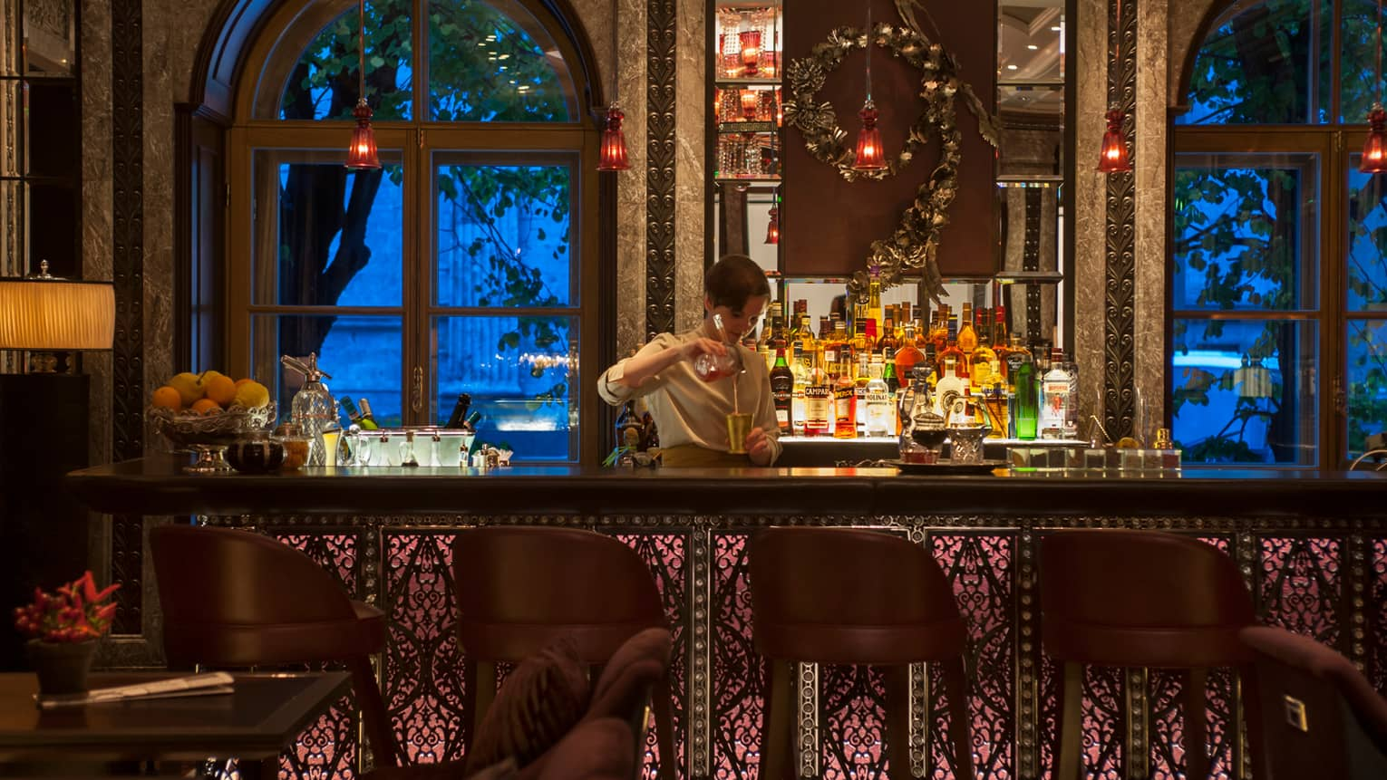 Percorso bartender mixes cocktails at dark bar under small red lights, by arched windows