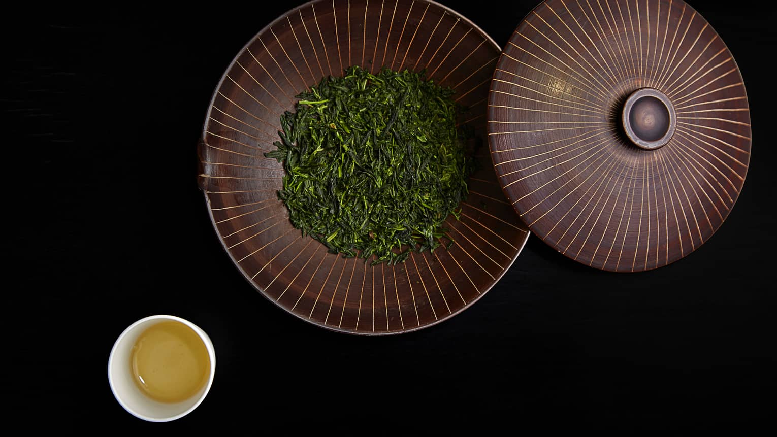Dried green leaves in large bowl with lid by small cup of tea