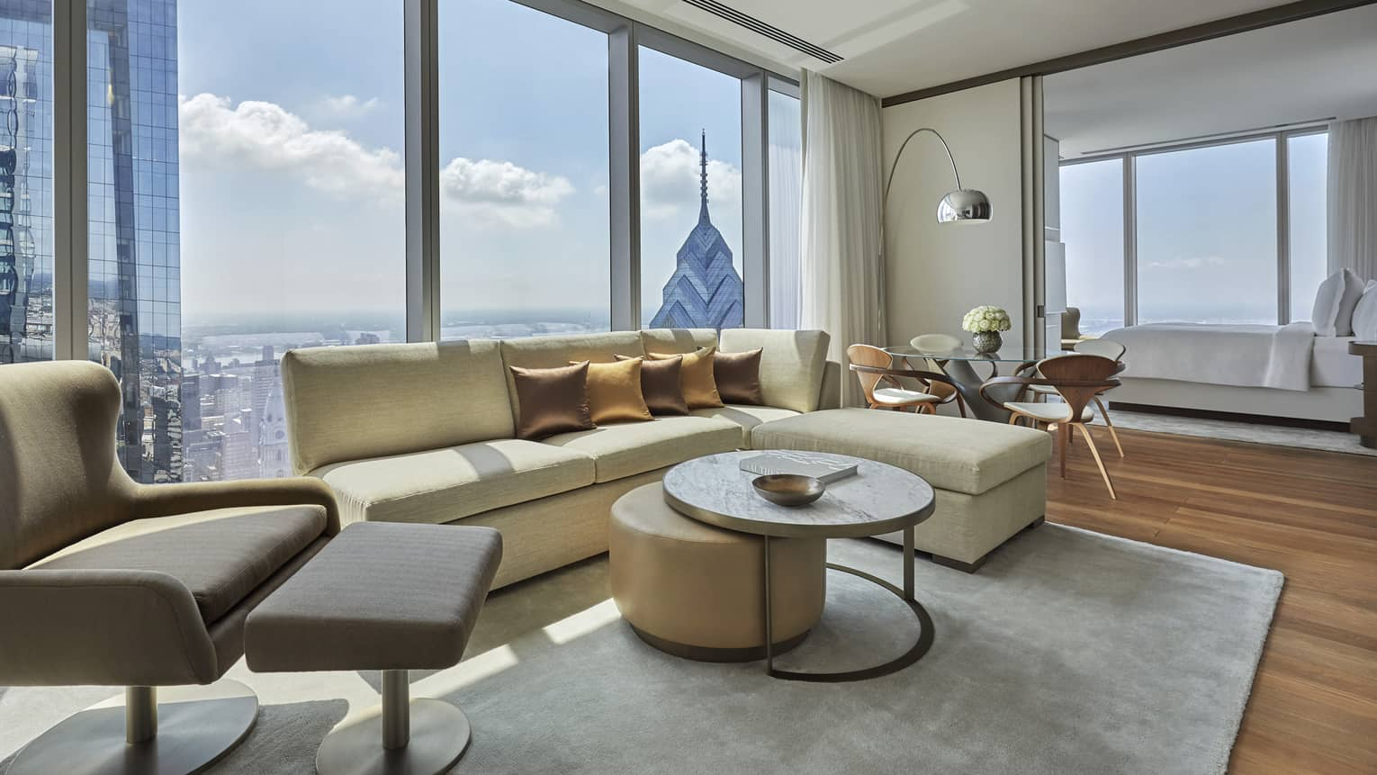 Modern living area with light yellow l-shaped sofa, arm chair, coffee table, Philadelphia city view