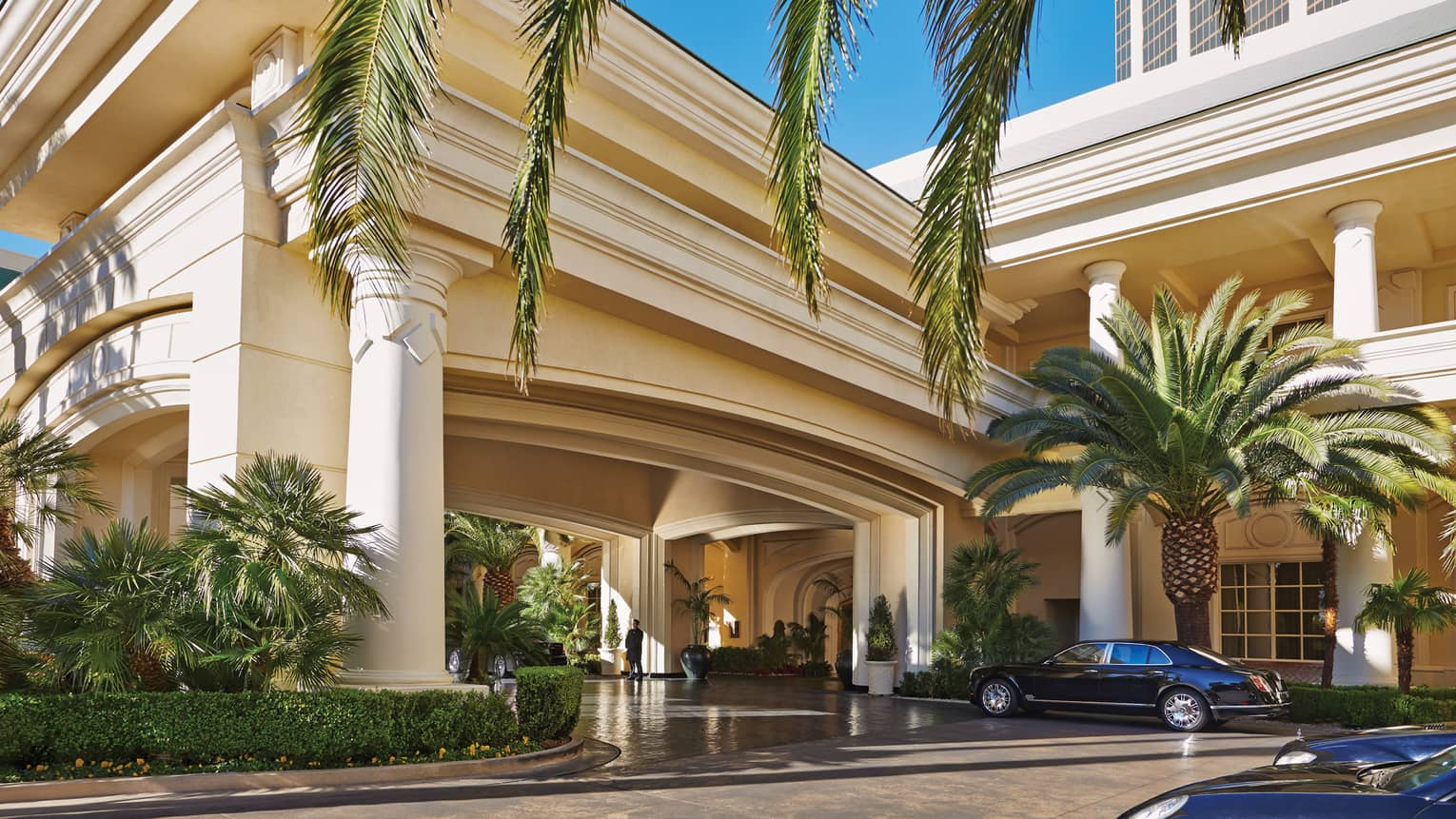 Luxury car parked by palm tree, large white pillars and front hotel entrance