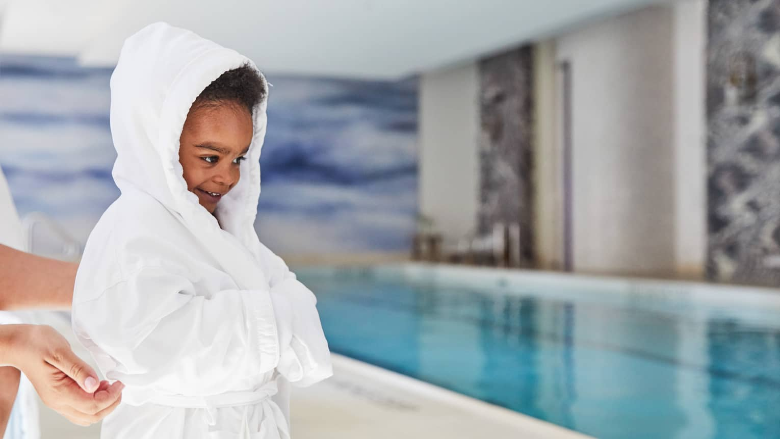 A close up of a child wearing a four seasons plush robe as she walks by the indoor pool at four seasons hotel new york downtown