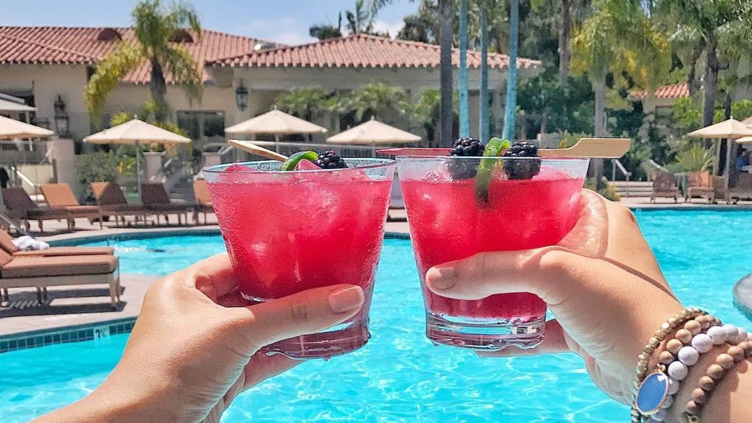 Hands toasting with red cocktails with fruity lime and blackberry garnish, in front of sunny swimming pool