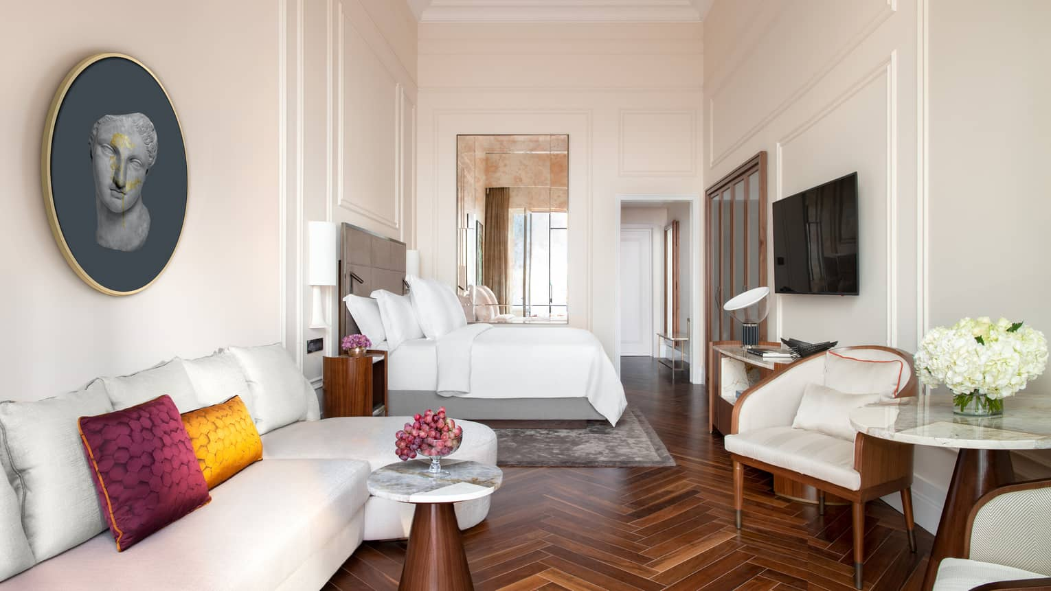 Suite with white king bed, high ceilings, wooden floors, sofa, table and two chairs