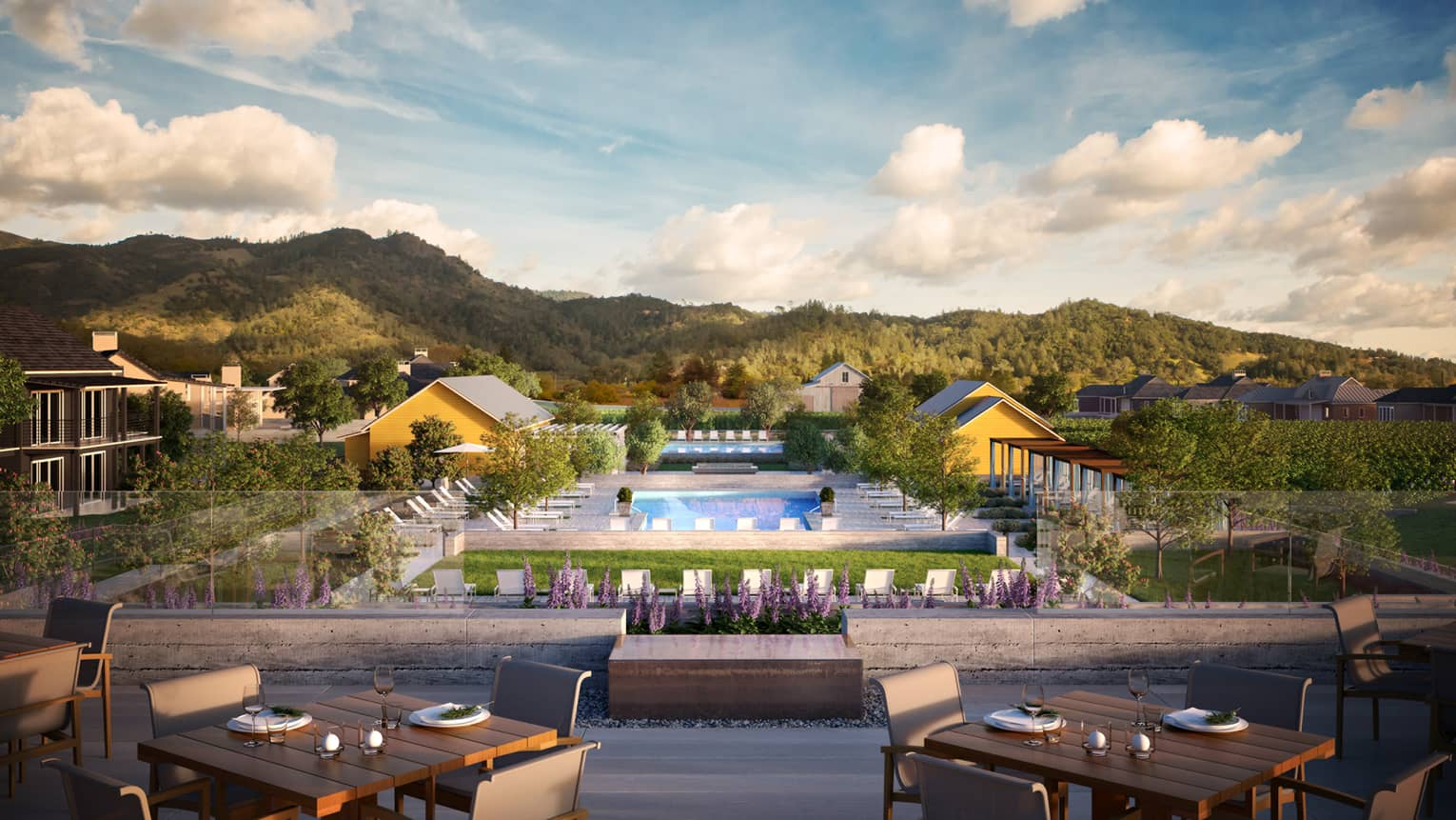 Patio dining tables overlooking resort pool, bungalows, green mountains