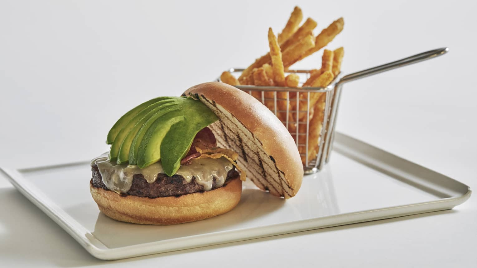 A beef burger with bacon jam, avocado and white cheddar, served with truffle parmesan fries