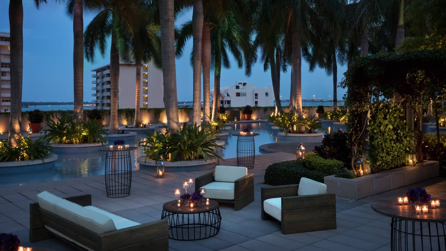 Plush white patio sofas and chairs, candle-lit tables under palm trees at night