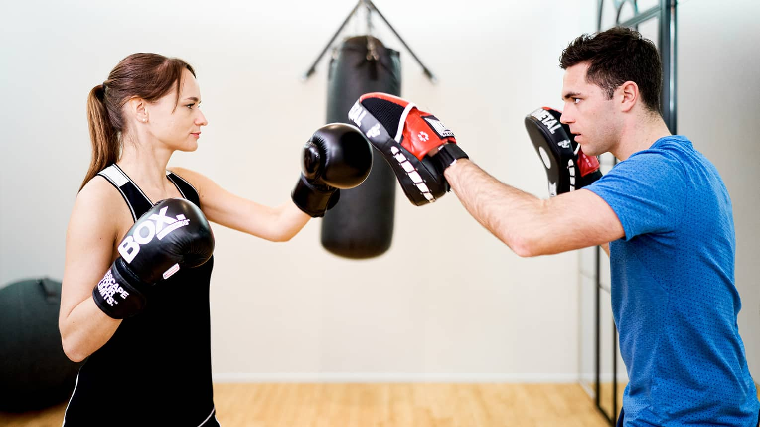 Gloved woman in black tank top sparring with man in blue shirt, heavy bag in backdrop