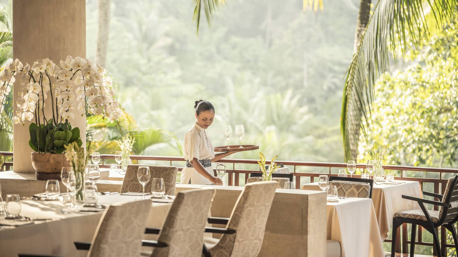 Hotel staff sets restaurant table in Ayung Terrace