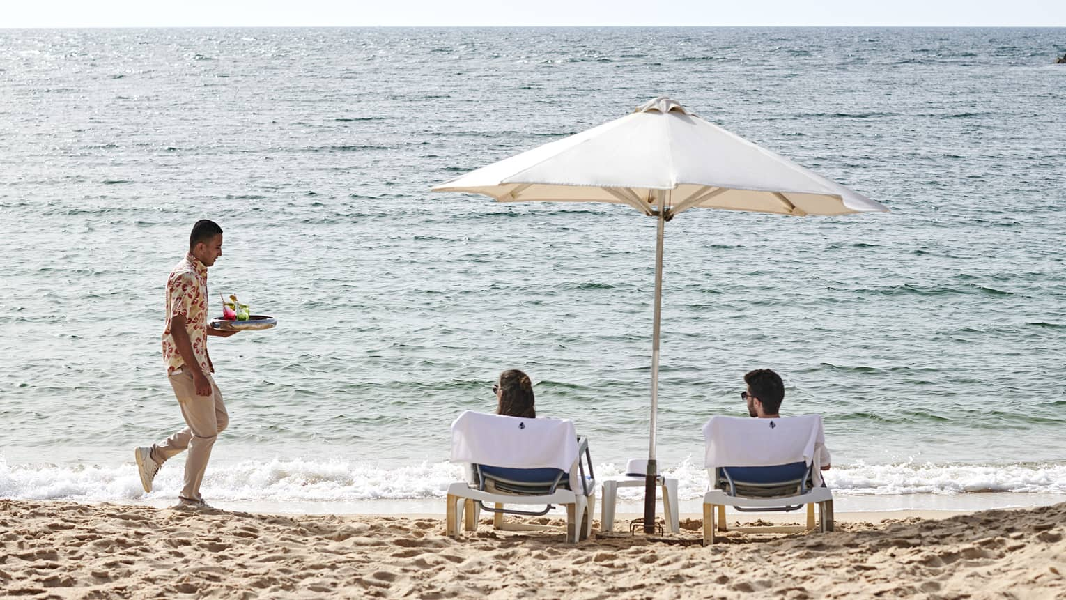a couple lounges on the beach in alexandria while a four seasons staff serves them refreshments