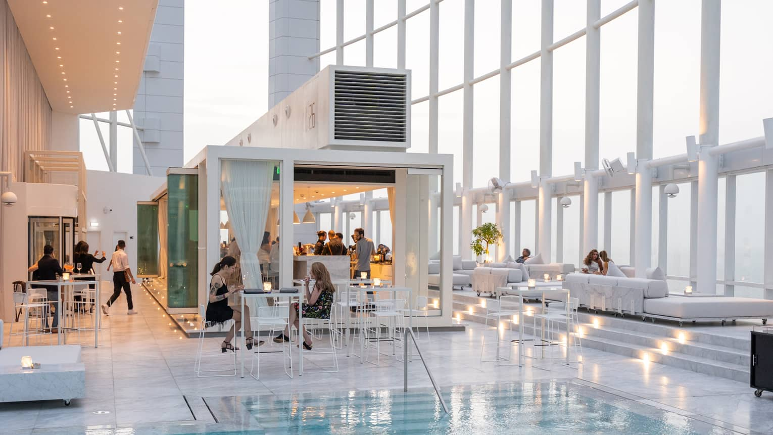 People mingle around a contemporary white bar next to pool