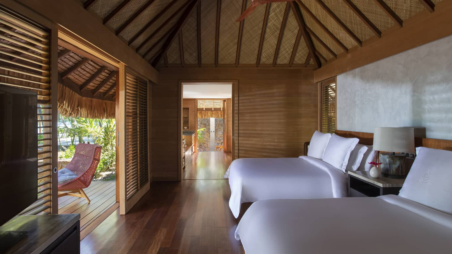 Two queen beds in a villa, with teak floors, a thatched roof and a walk-out patio