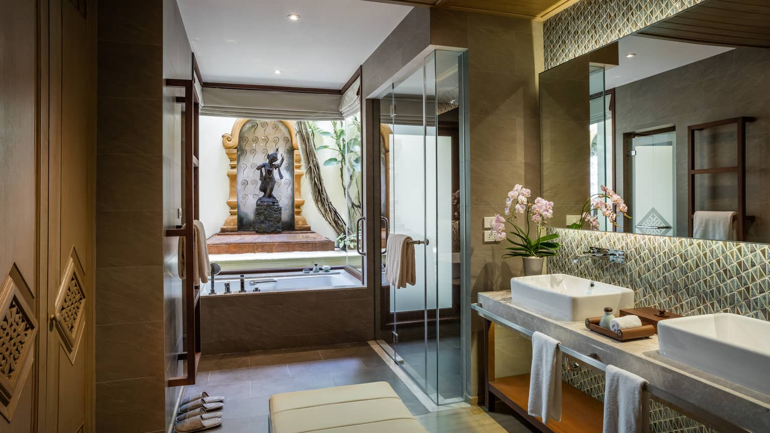 Garden Pavilion Room bathroom with double sink vanity, glass shower, tub under statue, monument